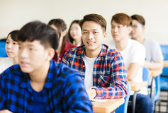 Estudiante universitario de sexo masculino asiático sonriente que se sienta con los compañeros de clase Fotografía de archivo