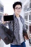 Estudiante universitario de sexo masculino con smartphone en la biblioteca Fotos de archivo