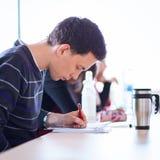 Estudiante universitario de sexo masculino joven, hermoso que se sienta en una sala de clase por completo Imagenes de archivo