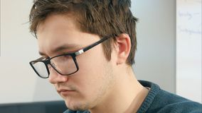 Estudiante universitario de sexo masculino joven que trabaja en su ordenador portátil en una sala de clase Imagenes de archivo