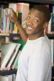 Estudiante universitario de sexo masculino que alcanza para un libro de la biblioteca fotos de archivo