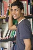 Estudiante universitario de sexo masculino que alcanza para un libro de la biblioteca Fotografía de archivo libre de regalías