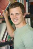Estudiante universitario de sexo masculino que alcanza para un libro de la biblioteca Imagen de archivo
