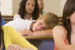 Estudiante universitario de sexo masculino que duerme a través de un lecutre foto de archivo libre de regalías