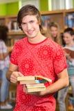Estudiante universitario de sexo masculino que sostiene los libros en biblioteca Imagenes de archivo