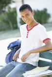 Estudiante universitario de sexo masculino Sitting On Bench con la mochila Fotos de archivo libres de regalías