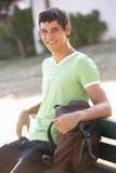 Estudiante universitario de sexo masculino Sitting On Bench con la mochila Imagenes de archivo