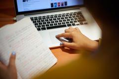 Estudiante universitario Doing Web Search de la muchacha en el ordenador portátil en la noche Imagen de archivo