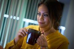 Estudiante universitario Drinking Coffee Studying de la muchacha en la noche Imágenes de archivo libres de regalías