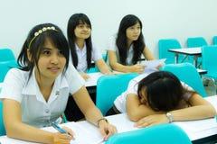 Estudiante universitario en uniforme que duerme en sala de clase Fotografía de archivo