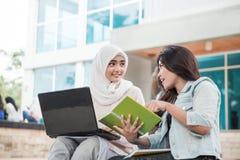 Estudiante universitario feliz dos que usa el ordenador portátil Foto de archivo libre de regalías