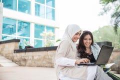 Estudiante universitario feliz dos que usa el ordenador portátil Foto de archivo