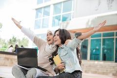 Estudiante universitario feliz dos que usa el ordenador portátil Fotografía de archivo libre de regalías