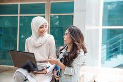 Estudiante universitario feliz dos que usa el ordenador portátil Imágenes de archivo libres de regalías