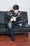 Estudiante universitario feliz que lee un libro y que bebe té Imagenes de archivo