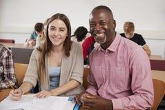 Estudiante universitario Has Individual Tuition del profesor In Classroom imagenes de archivo