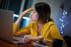 Estudiante universitario With Headache Studying de la muchacha en la noche Fotos de archivo libres de regalías