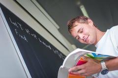 Estudiante universitario hermoso que soluciona un problema de matemáticas Imagenes de archivo