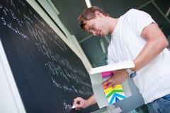 Estudiante universitario hermoso que soluciona un problema de matemáticas Foto de archivo