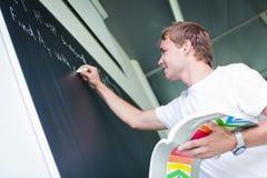 Estudiante universitario hermoso que soluciona un problema de matemáticas Fotos de archivo libres de regalías
