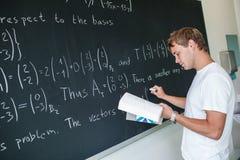 Estudiante universitario hermoso que soluciona un problema de matemáticas Imagen de archivo libre de regalías