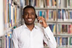 Estudiante universitario hermoso Using Mobile Phone en biblioteca Imagen de archivo