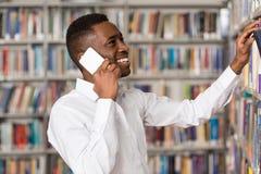 Estudiante universitario hermoso Using Mobile Phone en biblioteca Imágenes de archivo libres de regalías