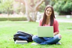 Estudiante universitario hispánico con la computadora portátil Imagenes de archivo