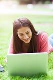 Estudiante universitario hispánico con la computadora portátil Foto de archivo