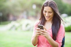 Estudiante universitario hispánico texting Imágenes de archivo libres de regalías