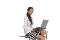Estudiante universitario indio con la computadora portátil en el escritorio Fotografía de archivo
