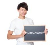 Estudiante universitario joven con la pizarra que muestra a escolares de una palabra Fotos de archivo