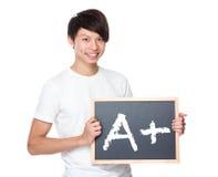 Estudiante universitario joven con la pizarra que muestra A más marca Fotografía de archivo libre de regalías