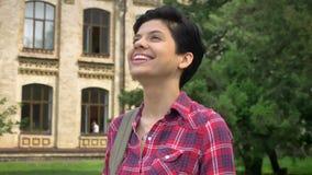 Estudiante universitario joven feliz con el pelo corto negro que sonríe y que se coloca en parque cerca de universidad almacen de video