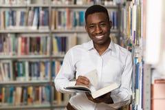 Estudiante universitario joven hermoso en una biblioteca imagen de archivo libre de regalías