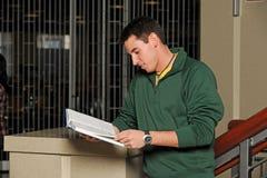 Estudiante universitario joven que lee un libro Imagenes de archivo