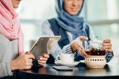 Estudiante universitario musulmán de sexo femenino que usa la tableta en café Fotografía de archivo