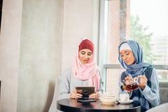 Estudiante universitario musulmán de sexo femenino que usa la tableta en café Imagen de archivo