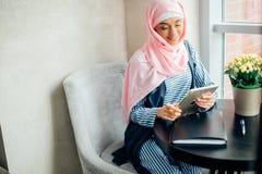 Estudiante universitario musulmán de sexo femenino que usa la tableta en café Fotos de archivo