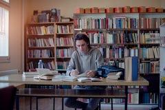 Estudiante universitario que aprende en biblioteca fotografía de archivo libre de regalías