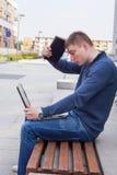 Estudiante universitario que aprende sobre el banco con el ordenador portátil Retrato de Fotografía de archivo