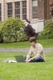 Estudiante universitario que estudia con el ordenador portátil y auriculares de botón en campus universitario Fotografía de archivo libre de regalías