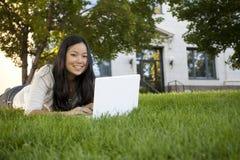 Estudiante universitario que estudia en la computadora portátil Imagen de archivo libre de regalías