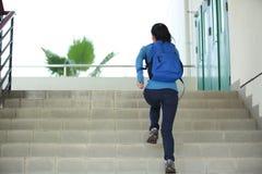 Estudiante universitario que funciona con para arriba las escaleras Imagen de archivo libre de regalías