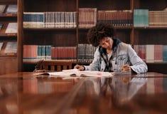 Estudiante universitario que hace la asignación en biblioteca foto de archivo libre de regalías