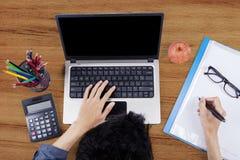 Estudiante universitario que hace la preparación en el escritorio Foto de archivo