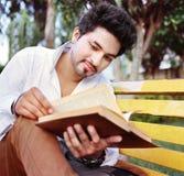 Estudiante universitario que lee sobre banco. Imagen de archivo