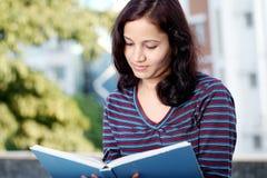 Estudiante universitario que lee un libro Fotografía de archivo libre de regalías