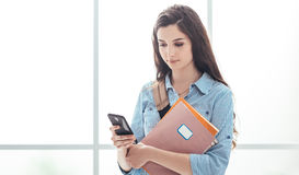 Estudiante universitario que manda un SMS con su teléfono Foto de archivo