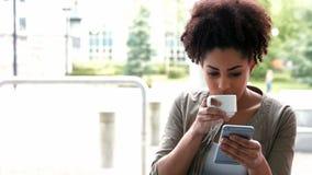 Estudiante universitario que manda un SMS en el café del campus almacen de video